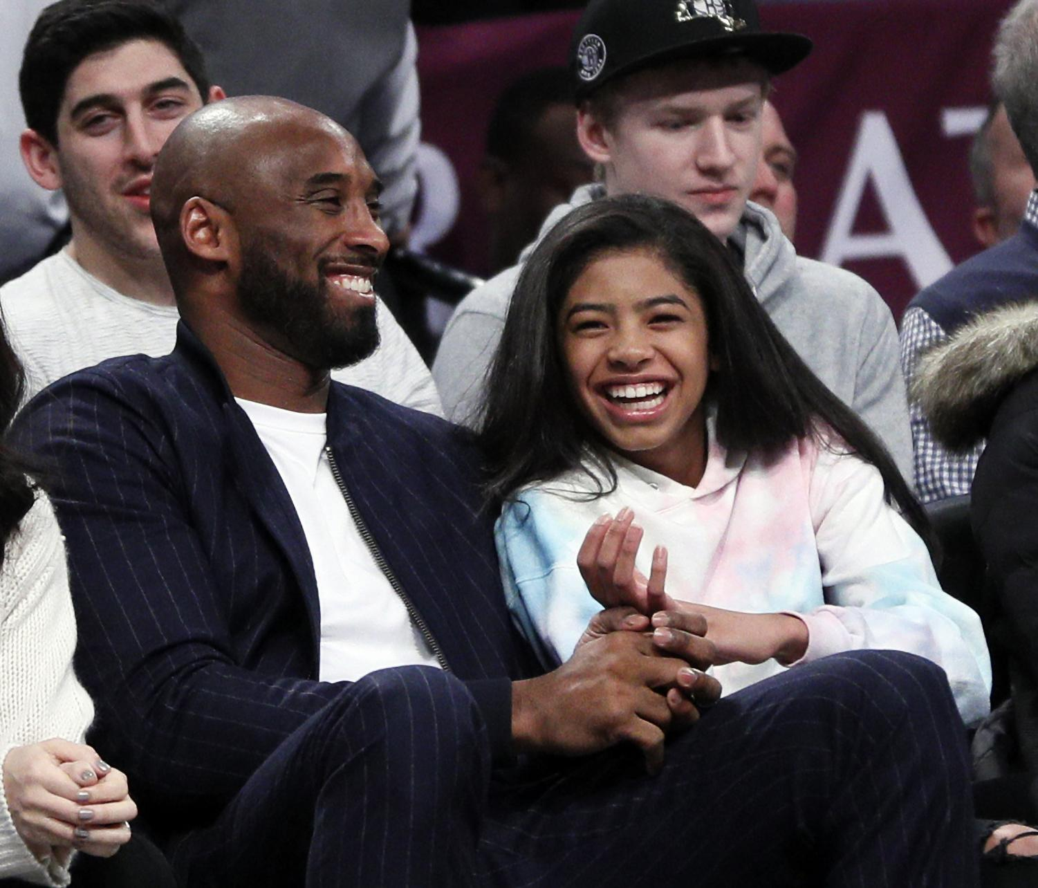 Kobe Bryant pictured with Gianna Bryant at a basketball game.